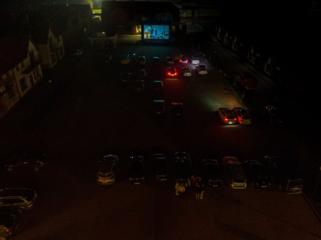 zdjęcie z lotu ptaka, samochody zaparkowane na placu, duży ekran kinowy, noc