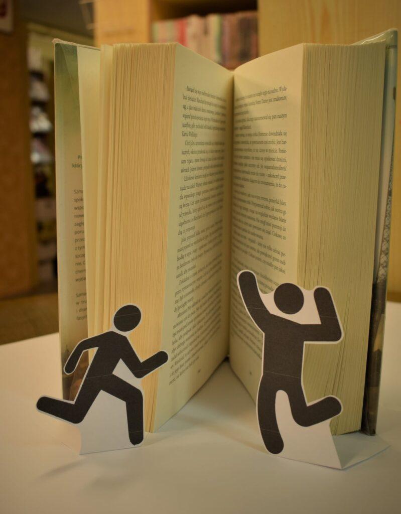 otwarta książka i czarne biegnące i skaczące ludziki