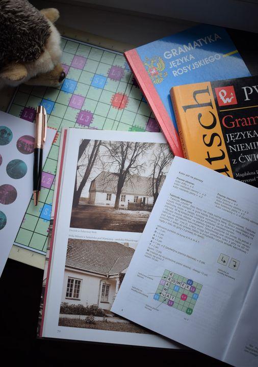 plansza do gry, otwarte książki, tabelki gramatyczne, długopis i pluszowy jeż