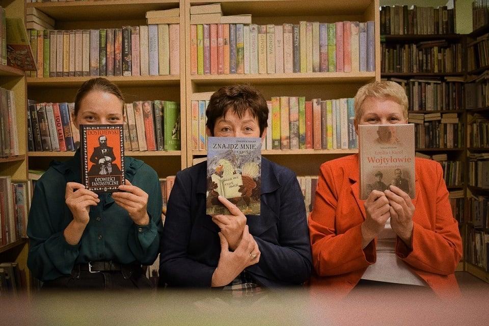 pani z biblioteki prezentują książki, które trzymają przed twarzą