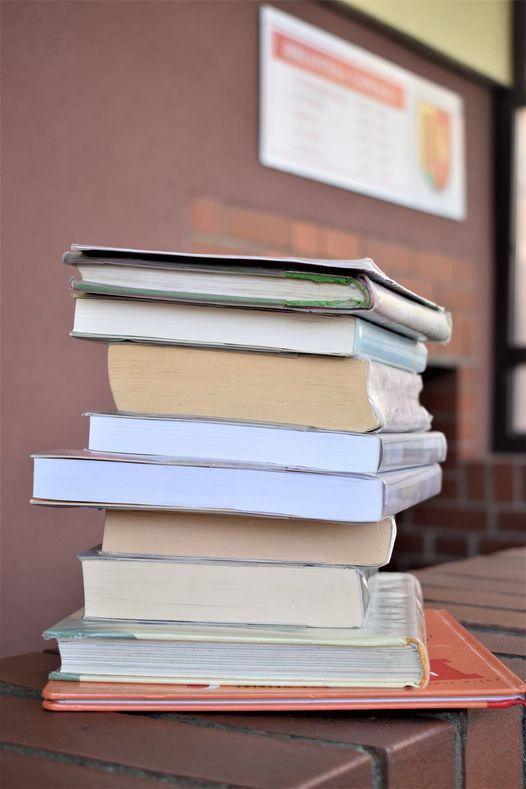 Książki jedna na drugiej na tle Gminnej Biblioteki Publicznej