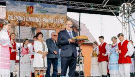 na pierwszym planie mężczyzna trzyma chleb na tacy i przemawia przez mikrofon na statywie, w tle osoby ubrane w stroje ludowe i baner gminno-parafialne