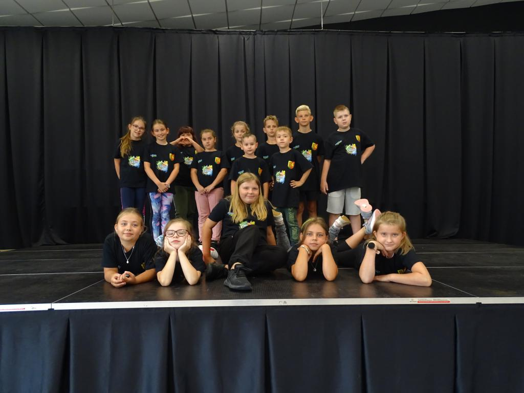 Dzieci w czarnych koszulkach z logo GOKSiAL i Gminy Pępowo stoją na scenie i pozują do zdjęcia